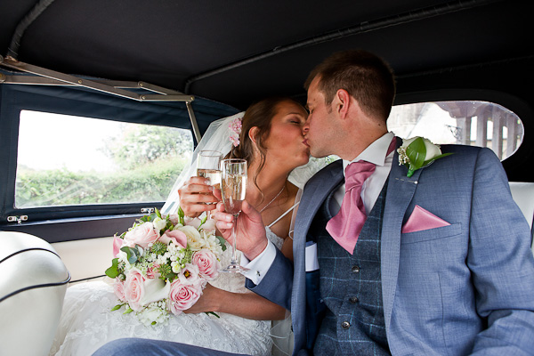 couple kissing in wedding car